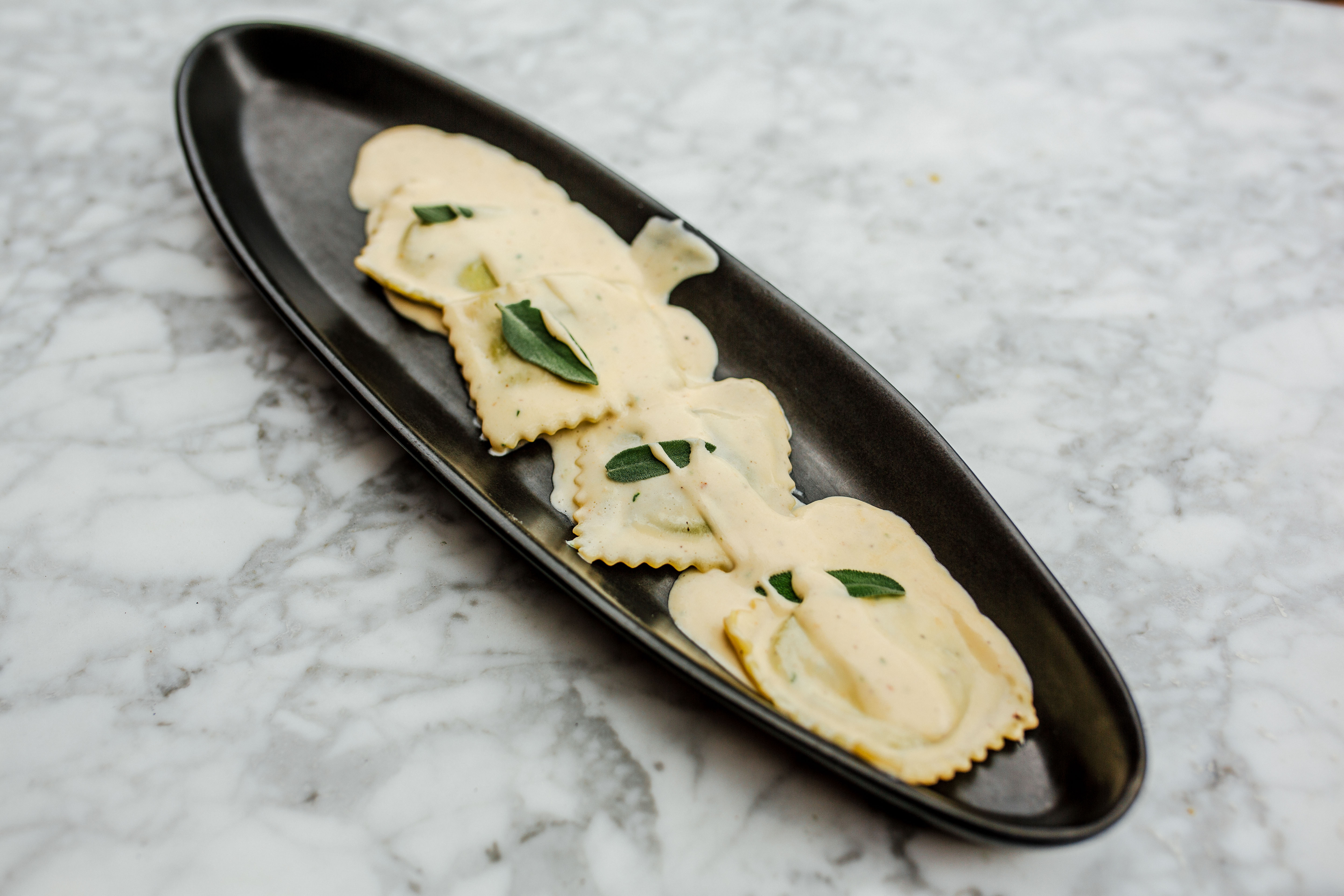 RAVIOLI: House Made Ravioli Filled with Ricotta Cheese and Spinach, Parmigiano, Cream, and Sage Sauce. Photography by Jamie Robbins.